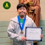 5th Grade student holding award certificate